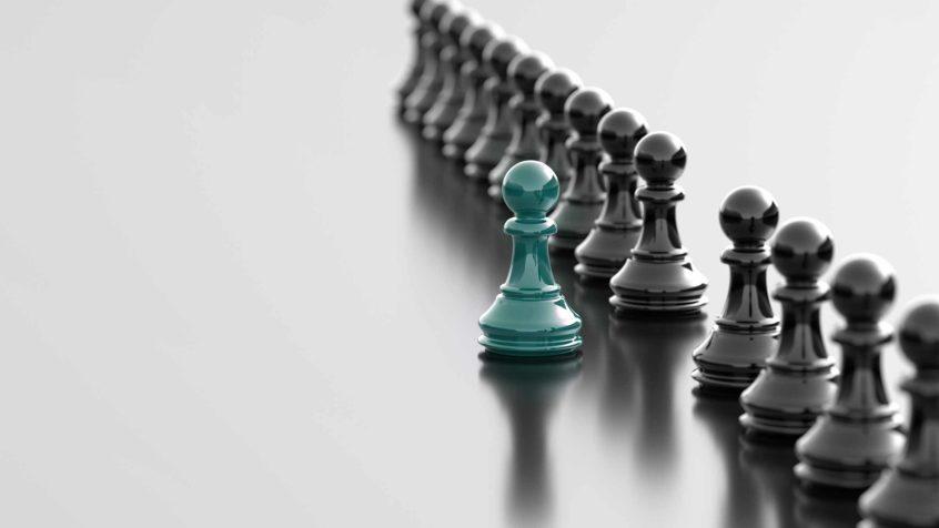 Svarta schackpjäser en rad grön ensam pjäs